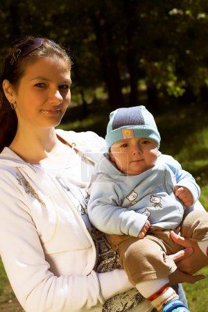 Photo pour Portrait d'une jeune belle mère avec son enfant lors de la promenade dans le parc en journée ensoleillée d'été - image libre de droit