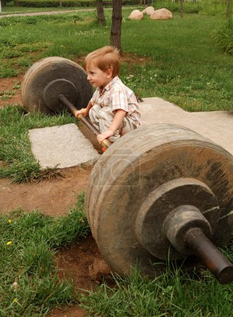 Photo for Little boy try lift up the barbell in the park - Royalty Free Image