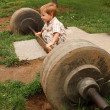 Little boy try lift up the barbell in the park...