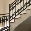 Shot of hotel stairs with banister and rusty wall...