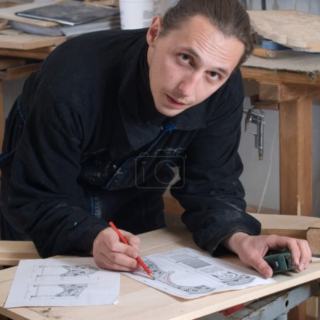 Photo pour Jeune menuisier dans son atelier avec plan de travail - image libre de droit