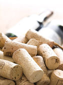 Corks next to the bottle of red wine