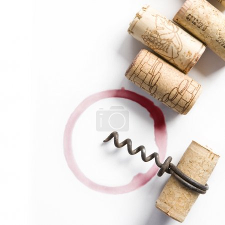 Photo for Wine corks, small corkscrew and round, red wine stain on white table cloth - Royalty Free Image