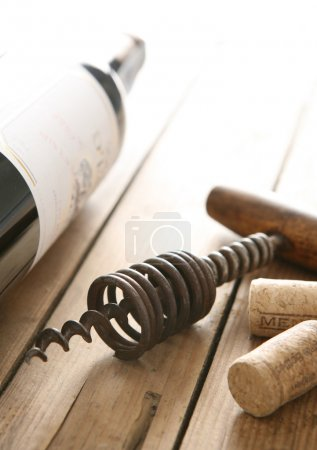 Corkscrew and bottle of red wine