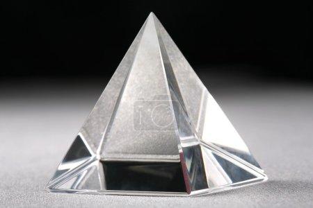 Photo pour Gros plan d'une pyramide de cristal sur fond gris et noir - image libre de droit