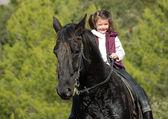 petite fille et son cheval noir