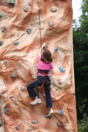 Photo pour Une fille escalade un mur . - image libre de droit