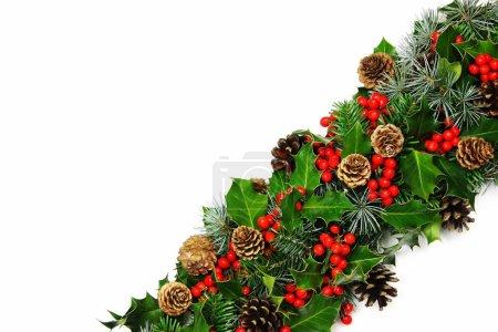 Photo pour Une bordure de Noël traditionnelle de houx naturel avec des baies rouges vives, cyprès, pins et conifères - image libre de droit