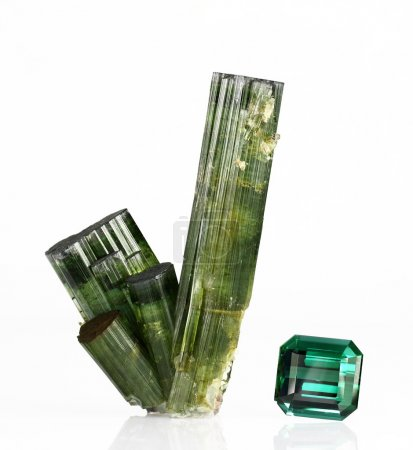 Photo for Verdite tourmaline crystals and a 26ct faceted gem on white. Used in optical and electrical equipment and metaphysically to energise the central nervous system. - Royalty Free Image
