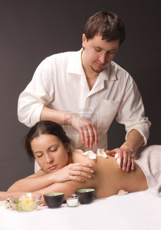 Photo for Massage therapist giving a massage to pretty woman. - Royalty Free Image