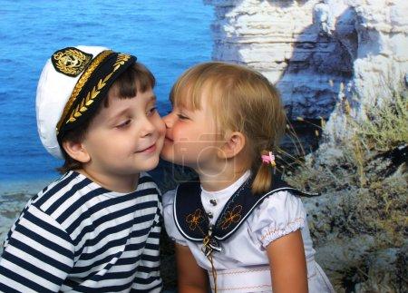 Mädchen küsst einen Jungen im Marinekleid