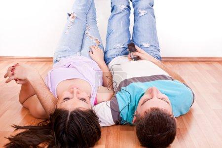 Photo pour Gros plan d'un jeune couple heureux couché sur la musique de détente et d'écoute de plancher - image libre de droit