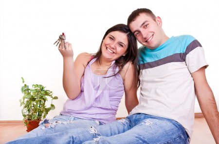 Young couple wiht keys in new apartment