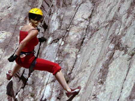 Photo pour La fille en costume rouge est engagée dans l'alpinisme rocheux - image libre de droit