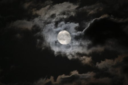 Photo for Full moon emerging from eerie white clouds against a black night sky - Royalty Free Image