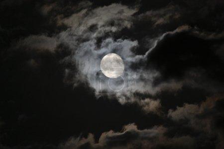 Full moon in eerie white clouds