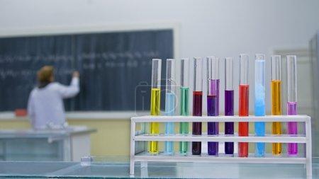 Photo pour Image dans un laboratoire de chimie de l'école.Focus sélectif sur les tubes au premier plan.En arrière-plan, il y a un élève qui écrit quelque chose sur le tableau noir . - image libre de droit