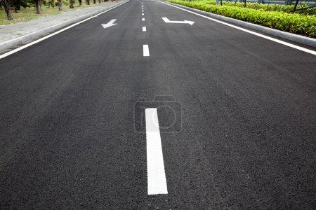 Photo pour Autoroute vide avec des flèches de signalisation sur la surface asphaltée - image libre de droit
