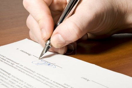 Photo pour Gros plan de la main tenant le crayon et la signature du contrat - image libre de droit