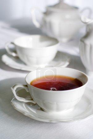 Photo pour Set de thé - deux tasses de thé, un thé chaud fumant, sugarbasin derrière. mettre l'accent sur la tasse de thé, faible profondeur de champ. - image libre de droit