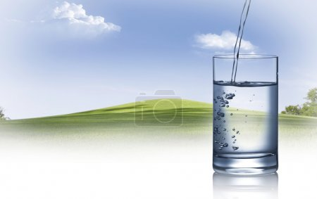 Photo pour Vue rapprochée du verre rempli d'eau sur fond d'été - image libre de droit