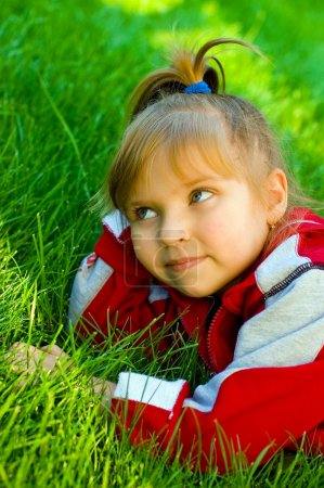 The small beautiful girl on a green lawn