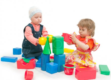 Foto de Dos niñas juegan dados sobre un fondo blanco - Imagen libre de derechos