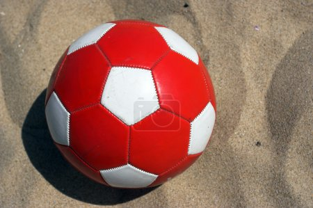 Photo for Red soccer ball on the sand - Royalty Free Image