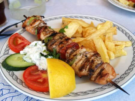 Plate with greek meal pork souvlaki in taverna...