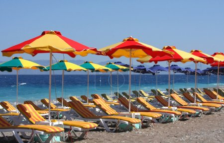 Beach with beds and colorful umbrellas