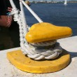 Yellow mooring hook with ship rope in the harbor...