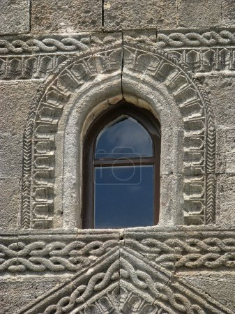Window and stone wall with carving