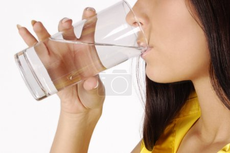 Beautiful woman drinks water from glass