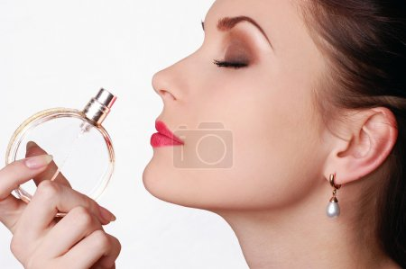 Photo for Beautiful young woman smelling her perfume isolated on white - Royalty Free Image