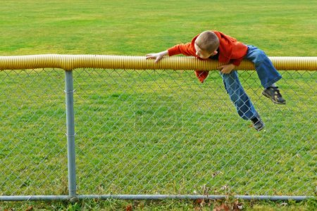 Young boy climbing chain link fence