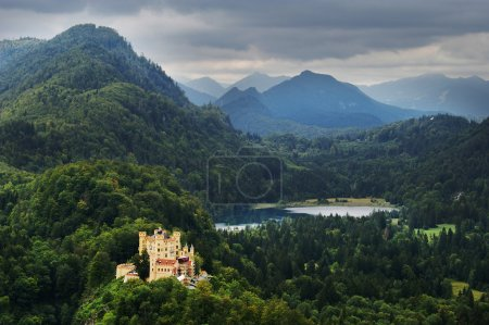 Hohenschwangau castle in bavaria on forest hills with mountain peaks overcast day