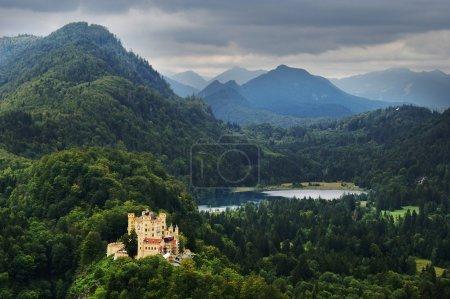 Photo pour Château de Hohenschwangau en bavière sur les collines forestières avec des sommets de montagne journée nuageuse - image libre de droit