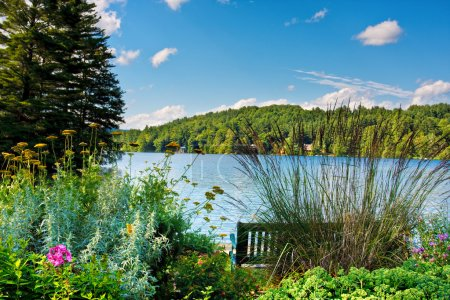 Photo for A scenic lake in the mountains. There is a bench and a flower garden in the foreground. - Royalty Free Image