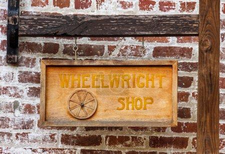 Foto de Una muestra de la tienda wheelwright colgado delante de una pared de ladrillo - Imagen libre de derechos