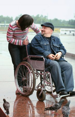 Man in a wheelchair talking with woman