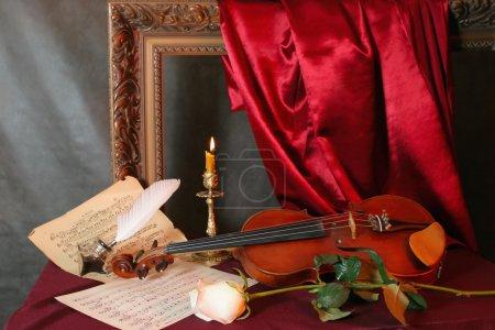 Photo pour Nature morte romantique avec violon, fleur et partitions de musique - image libre de droit