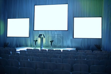 Photo for Empty big conference hall with podium and three screens - Royalty Free Image