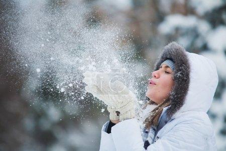 Photo pour Belle femme soufflant dans la neige - image libre de droit