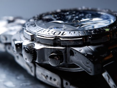 Closeup of wet metal wrist watch....