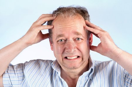 Photo for A middle-aged man is suffering from a migraine or bad news. - Royalty Free Image