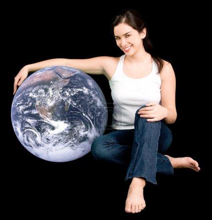 Photo pour Une jeune femme habillée par hasard tient la terre comme un ami précieux. photo de la terre a été fourni par la nasa et de l'autorisation est accordée pour l'utilisation de stock - image libre de droit