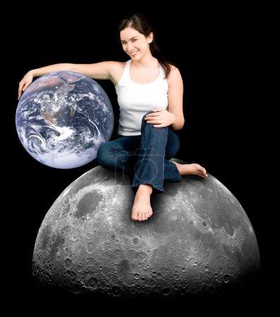 Photo pour Une jeune femme habillée par hasard est assis sur la lune en tenant la terre comme un ami précieux. - image libre de droit
