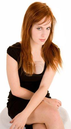 Photo pour Une dame aux cheveux rouges sexy est assise sur un banc regardant de côté la caméra . - image libre de droit