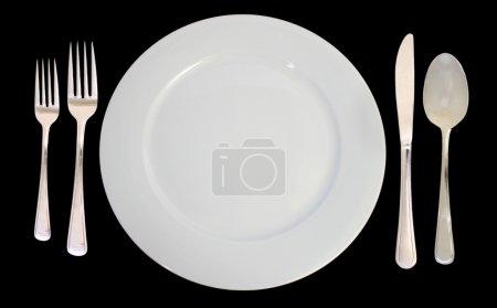 Photo pour C'est un cadre de lieu comprenant une assiette blanche et argenterie sur un fond noir . - image libre de droit