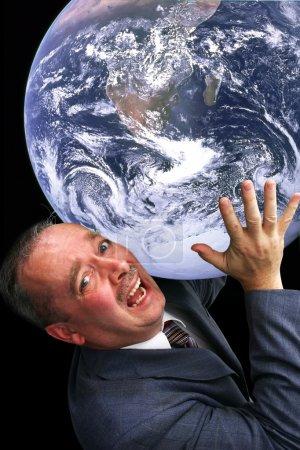 Photo pour Un homme est douloureusement portant le monde sur l'épaule. la photo de la terre a été fournie par la nasa et de l'autorisation est accordée pour l'utilisation de stock. - image libre de droit